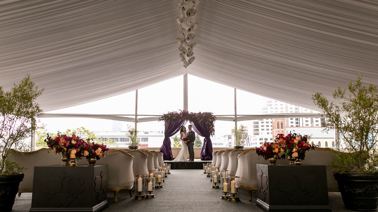 A bridal couple poses under their handcrafted wedding mantle at The St. Regis San Francisco