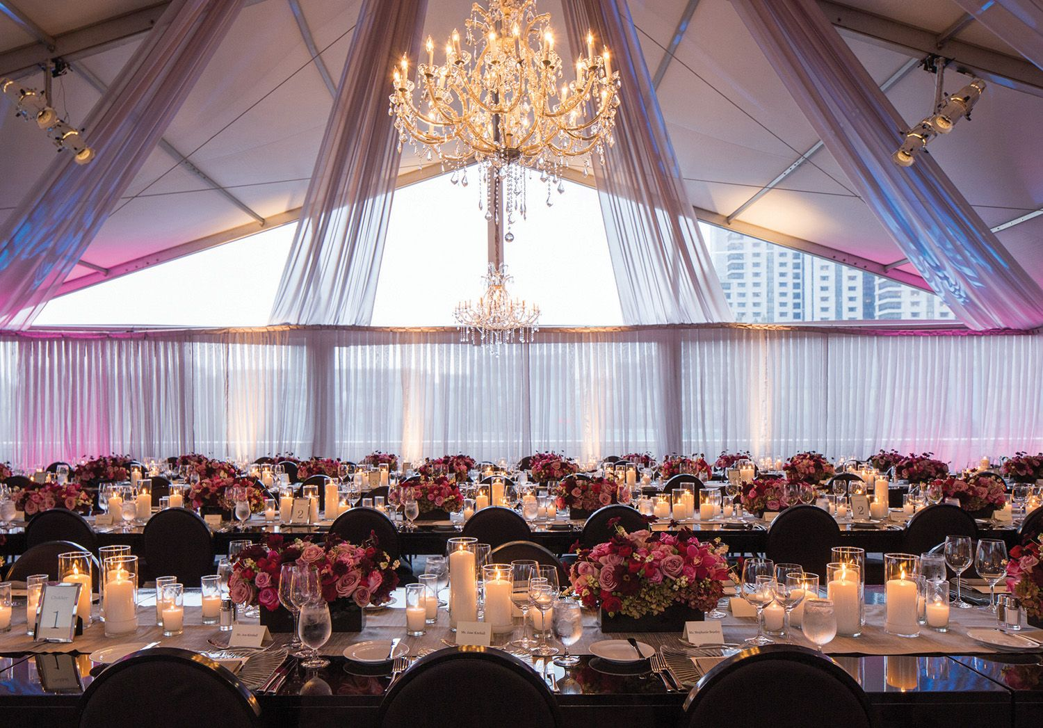 A crystal chandelier hangs over meticulously decorated tables at a St. Regis wedding