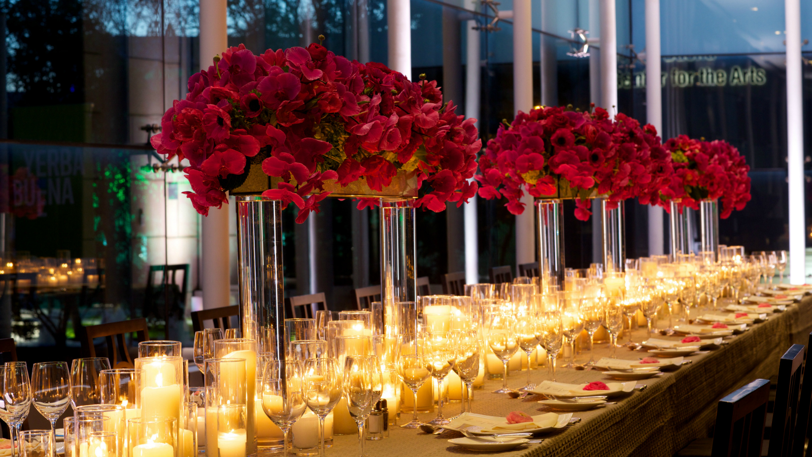 Impeccable floral arrangements and subtly lit candles set as centerpieces along an inviting wedding table at the St. Regis hotel